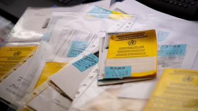 Zahlreiche Impfpässe liegen in einer Apotheke in einem Büro auf einem Tisch. (Archivbild)