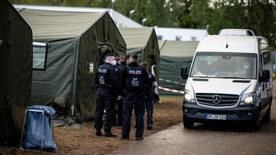 Polizisten in der Erstaufnahmeeinrichtung Eisenhüttenstadt neben einem Zelt für neu ankommende Asylsuchende.
