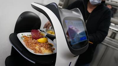 """Der Servierroboter """"Bella"""" wird in der Küche des Restaurants in Grömitz mit  Gerichten für die Gäste beladen."""
