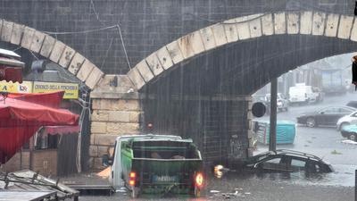 Fahrzeuge stehen auf einer überschwemmten Straße in Cantania.