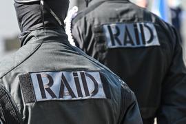 """Polizisten mit der Aufschrift """"Raid"""" auf der Uniform."""