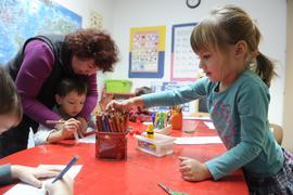 Kinder malen an einem Tisch, eine Frau hilft mit