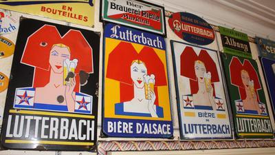 Emailleschild der Brasserie Lutterbach aus dem Südelsass: Trachten-Mädchen mit Schlupf im art déco-Stil.