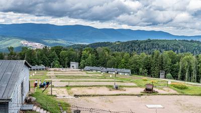 Lagertor und Blick über das Lager. Auf den Erdflächen standen einst Häftlingsbaracken.