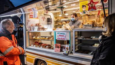 Mann kauft Brot bei einem mobilen Bäcker
