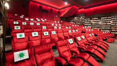ARCHIV - 23.07.2020, Niedersachsen, Hannover: Einzelne Sitzplätze in einem Kinosaal vom Kino Astor Grand Cinema sind mit Zetteln mit aufgedrucktem angedeuteten Virus-Symbol abgesperrt, damit Kino-Besucher einen Abstand von 1,5 Meter zueinander einhalten können. (zu dpa Kinobranche appelliert an Merkel: Abstandsregeln lockern) Foto: Julian Stratenschulte/dpa +++ dpa-Bildfunk +++ | Verwendung weltweit