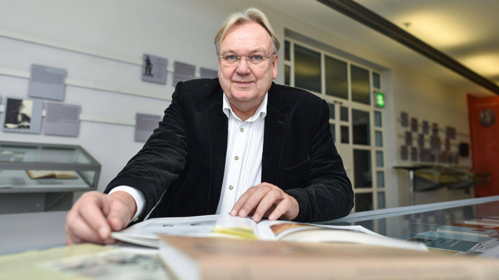 """Der Literaturwissenschaftler und Leiter des """"Museums für Literatur am Oberrhein"""", Hansgeorg Schmidt-Bergmann, sitzt am 15.12.2014 in Karlsruhe (Baden-Württemberg) mit Büchern in den Museumsräumen. Foto: Uwe Anspach/dpa (zu dpa «Lyrik mit Gänsehaut-Garantie: Literatur lebt von unten» 15.02.2015) +++(c) dpa - Bildfunk+++"""