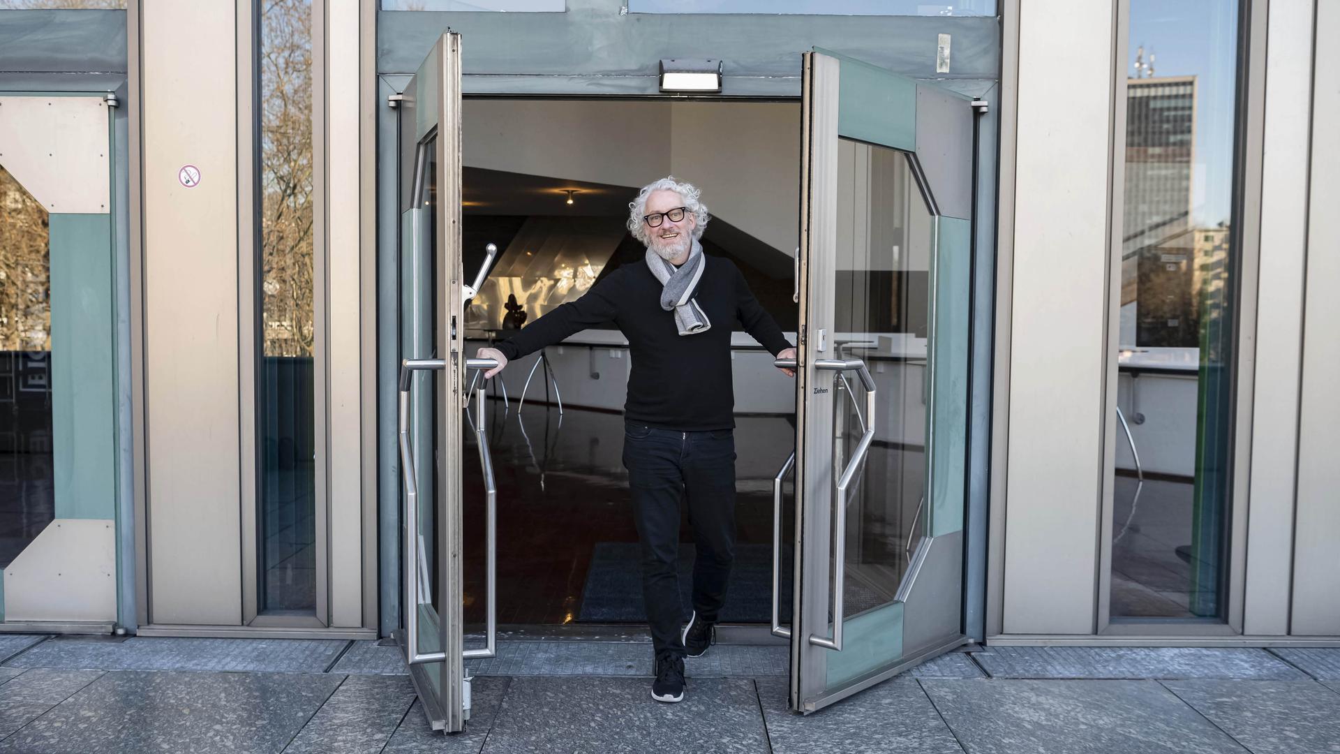 Peter Spuhler, Generalintendant des Badischen Staatstheaters Karlsruhe, steht bei dem Theater an der Flügeltür zu einem Balkon.