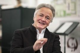 Der Rektor der Musikhochschule Karlsruhe lächelt in die Kamera und hebt dabei leicht die Hand