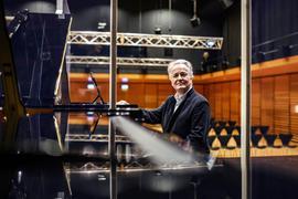 Der Pianist Hartmut Höll, Rektor der Musikhochschule Karlsruhe,  aufgenommen im leeren, hell beleuchteten Wolfgang Rihm Forum.