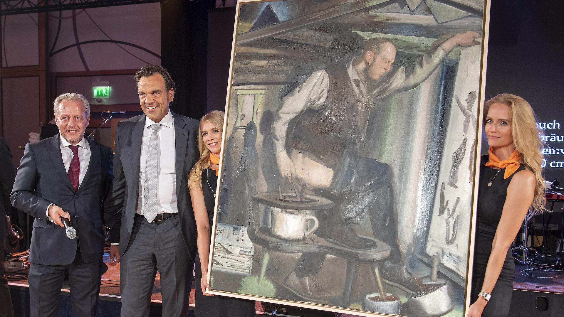 Veranstalter Steffen Göpel (l) und Unternehmer Christoph Gröner (2.v.l.) stehen neben zwei Damen, die das Gemälde «Der Anbräuner» von Neo Rauch präsentieren.  ACHTUNG: Nur zur redaktionellen Verwendung im Zusammenhang mit der aktuellen Berichterstattung über die Auktion und nur mit vollständiger Nennung des vorstehenden Credits. Kein Verkauf, Keine Archivierung! +++ dpa-Bildfunk +++  