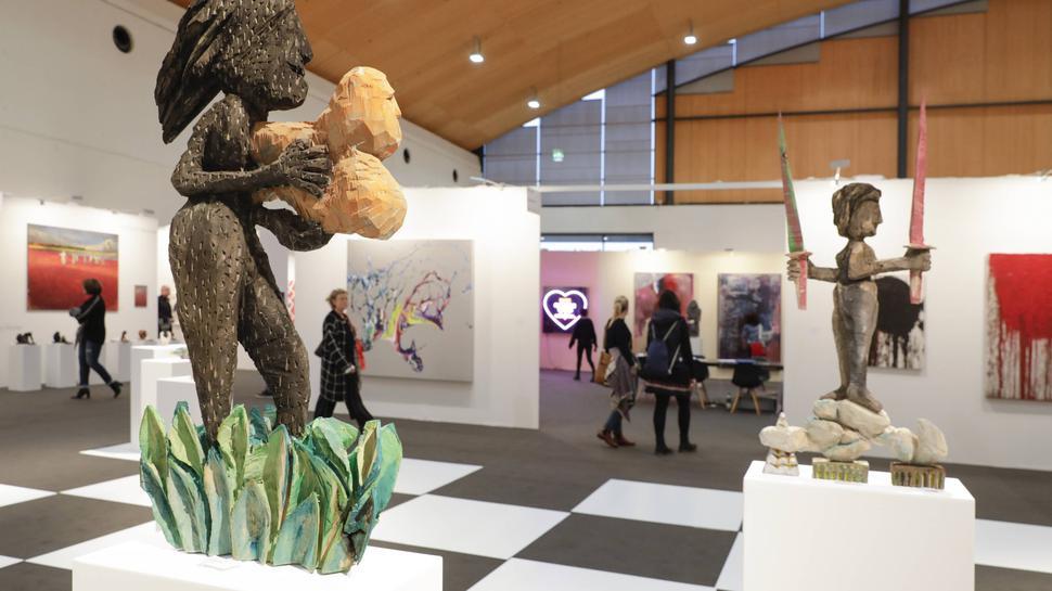 Blick in eine Messehalle der art Karlsruhe. Im Vordergrund expressiv gestaltete, bunt bemalte Skulpturen, im Hintergrund Stellwände mit Bildern.