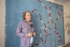Ein Mann mit lockigem Blondhaar vor einem großen Gemälde, das auf blauem Grund ein weiß-rotes Flatterband zeigt