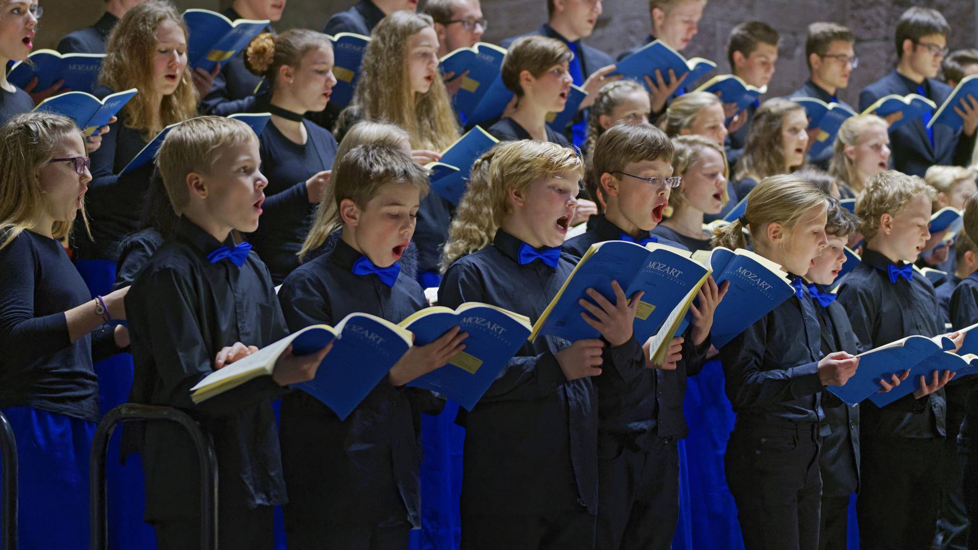 Singende Mädchen und Jungen mit blauen Notenheften in den Händen.