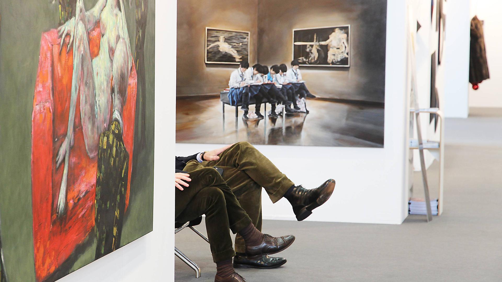 Blick auf eine Koje der art Karlsruhe. Links ein Gemälde, hinten ein Gemälde, dazwischen zwei Paar Männerbeine in Cordhosen; die Männer selbst sieht man nicht.