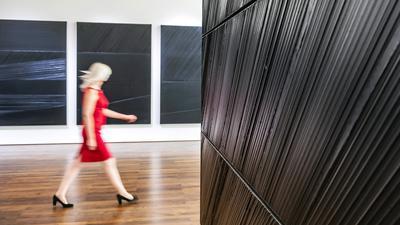 Eine blonde Frau in totem Kleid geht schnellen Schritts durch eine Ausstellung mit schwarzen Bildern.