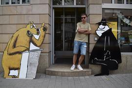 Steffen Butz neben zwei großen Cartoonfiguren in einem Hauseingang.