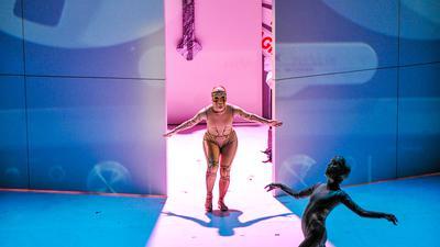 Zwei Tänzer vor einer blauen und rosafarbenen Kulisse. Im Hintergrund ein großes Kreuz.