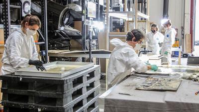 Arbeit an der Rettung schwer beschädigter Museumsobjekte in einer Lagerhalle des ZKM Karlsruhe