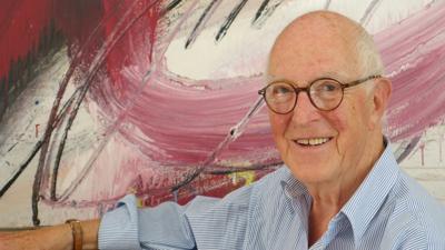 Ein Mann mit Glatze und Brille vor einem abstrakten Gemälde.