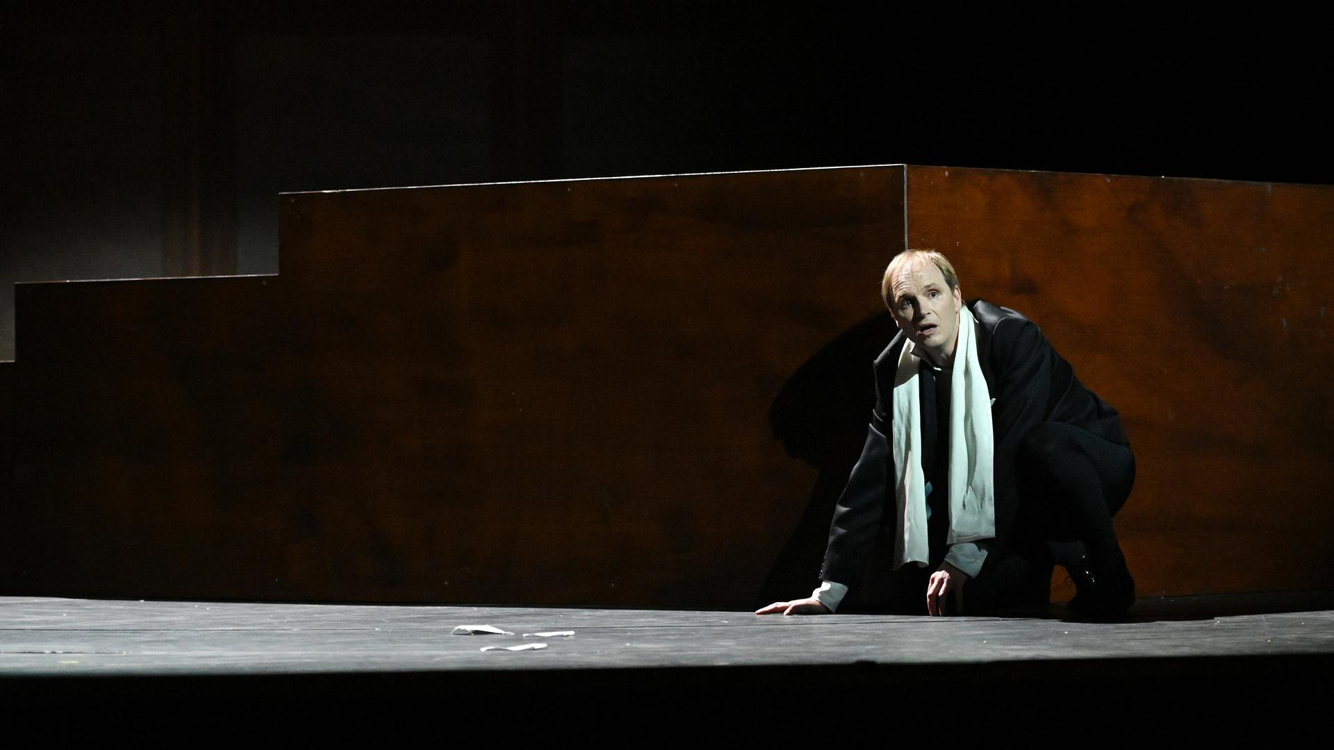 Ein Mann mit weißem Schal kauert auf dem Boden und schaut fragend in die Runde.