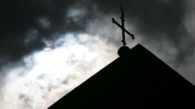 Im Gegenlicht und vor wolkenverhangenem Himmel ist die Kirchturmspitze eines Doms mit Kreuz zu sehen.