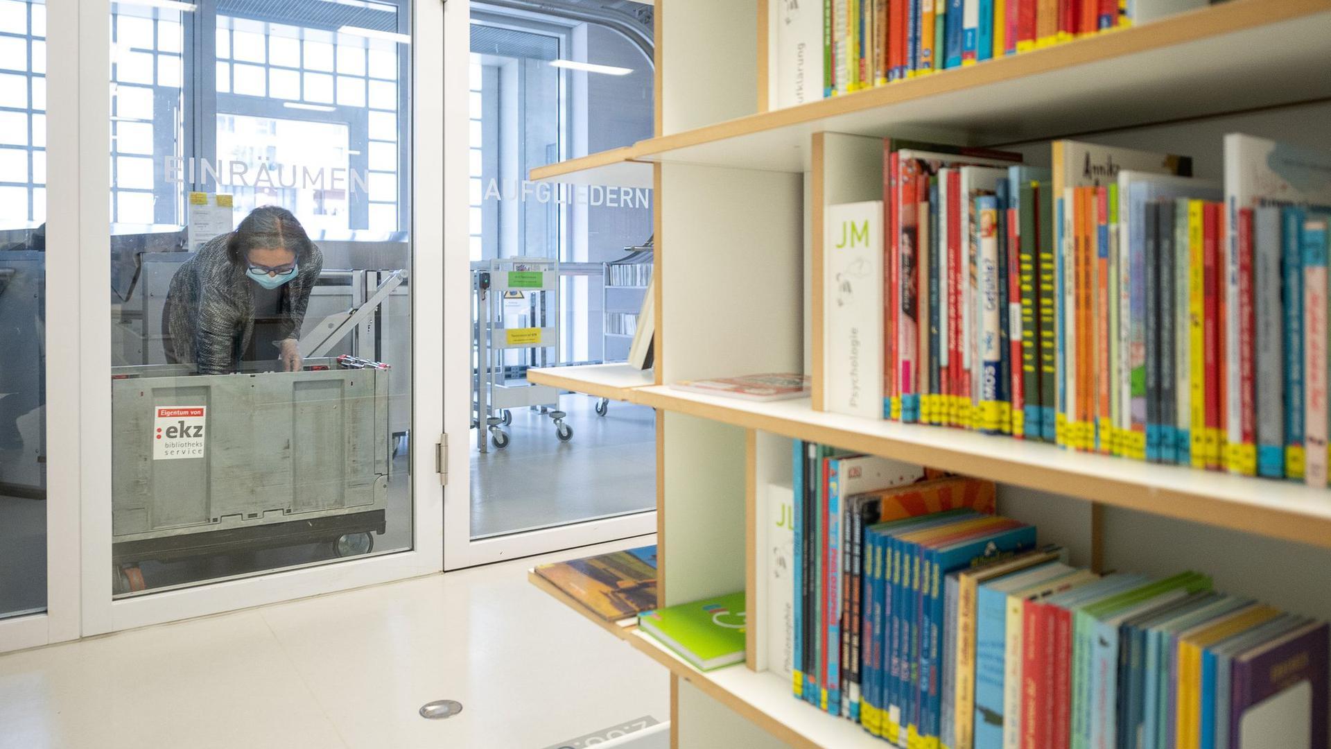 Eine Mitarbeiterin legt in einer Bibliothek ein Buch in die Quarantänebox.