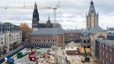 """Blick auf die Baustelle """"Archäologische Zone - Jüdisches Museum MiQua"""" - im Hintergrund der Kölner Dom und das Historische Rathaus."""