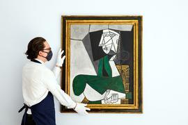 """Ein Mitarbeiter von Sotheby's hängt das Gemälde """"Femme assise en costume"""" von Pablo Picasso (gemalt 1953) auf."""