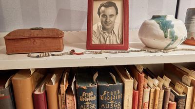 """Ein Bilderrahmen mit einem Foto des Schriftstellers Wolfgang Borchert steht auf einem Bücherregal in der """"Borchert-Box"""". Am 20. Mai wäre Borchert 100 Jahre alt geworden."""