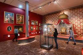 """Im Badischen Landesmuseum im Karlsruher Schloss betrachten Menschen den neuen Sammlungsbereich """"Schloss und Hof: Der Thronsaal – neu präsentiert""""."""