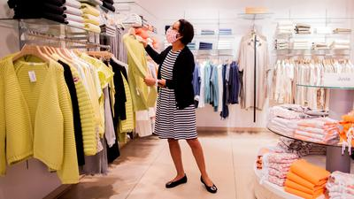 Eine Verkäuferin mit Mund- und Nasenschutz arbeitet im Modehaus Schnitzler am Prinzipalmarkt. +++ dpa-Bildfunk +++