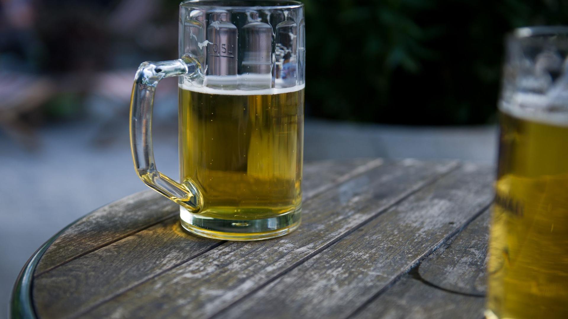 Zwei Bierkrüge stehen in einem Biergarten auf einem Tisch.
