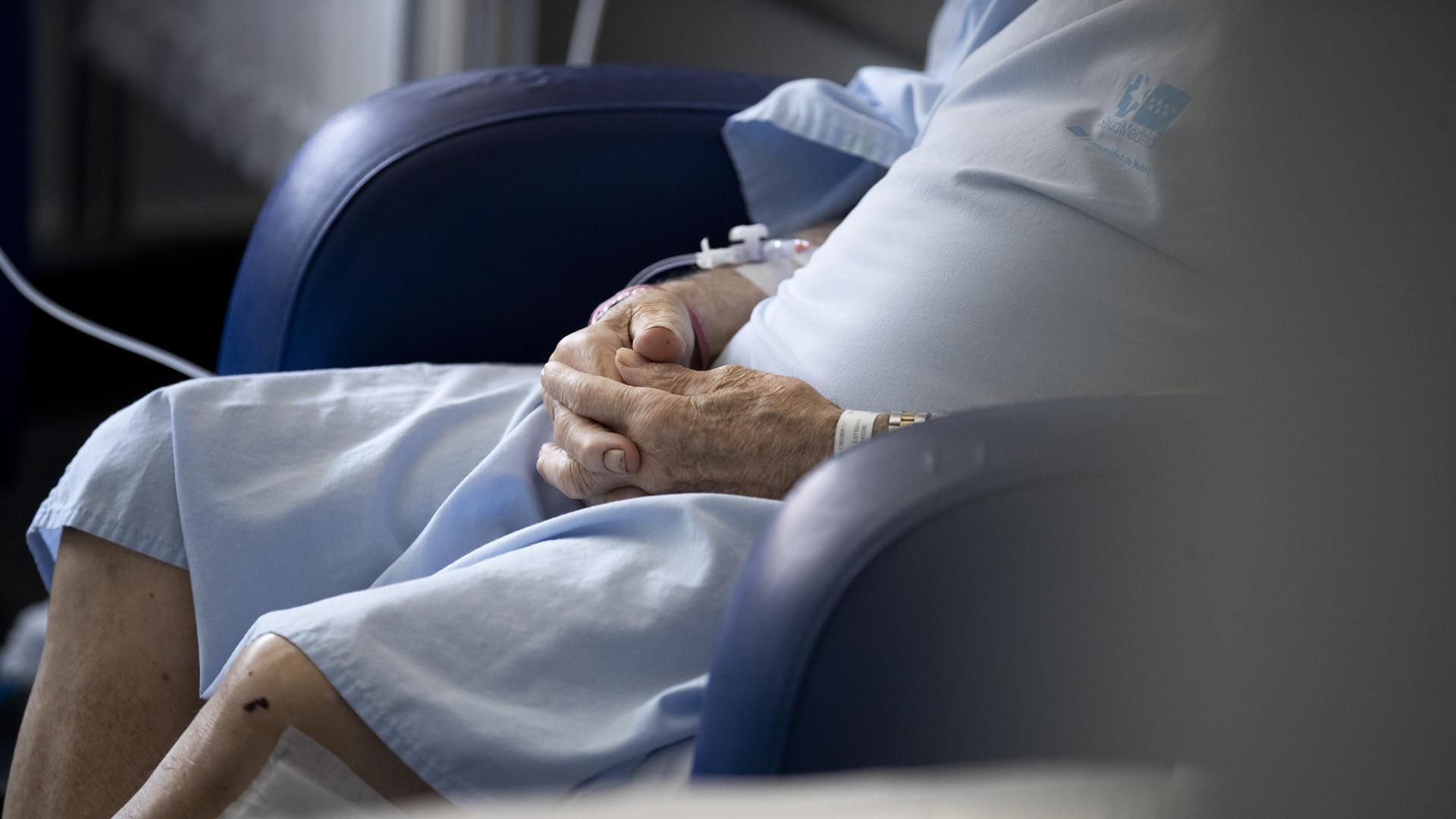 Ein älterer Patient sitzt in einem Krankenhauszimmer