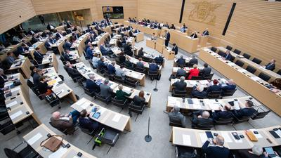 Abgeordnete sitzen im Stuttgarter Landtag auf ihren Plätzen.