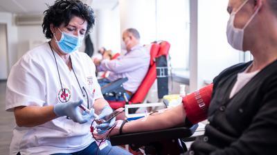 Martina Schimm, Mitarbeiterin des Blutspendezentrums des Deutschen Roten Kreuzes, nimmt während einer Spende eine Probe. Spenderblut ist auch in der Corona-Pandemie wichtig. Darauf will NRW-Gesundheitsminister Laumann mit Vertretern des Deutschen Roten Kreuzes (DRK) und der Uniklinik aufmerksam machen. +++ dpa-Bildfunk +++
