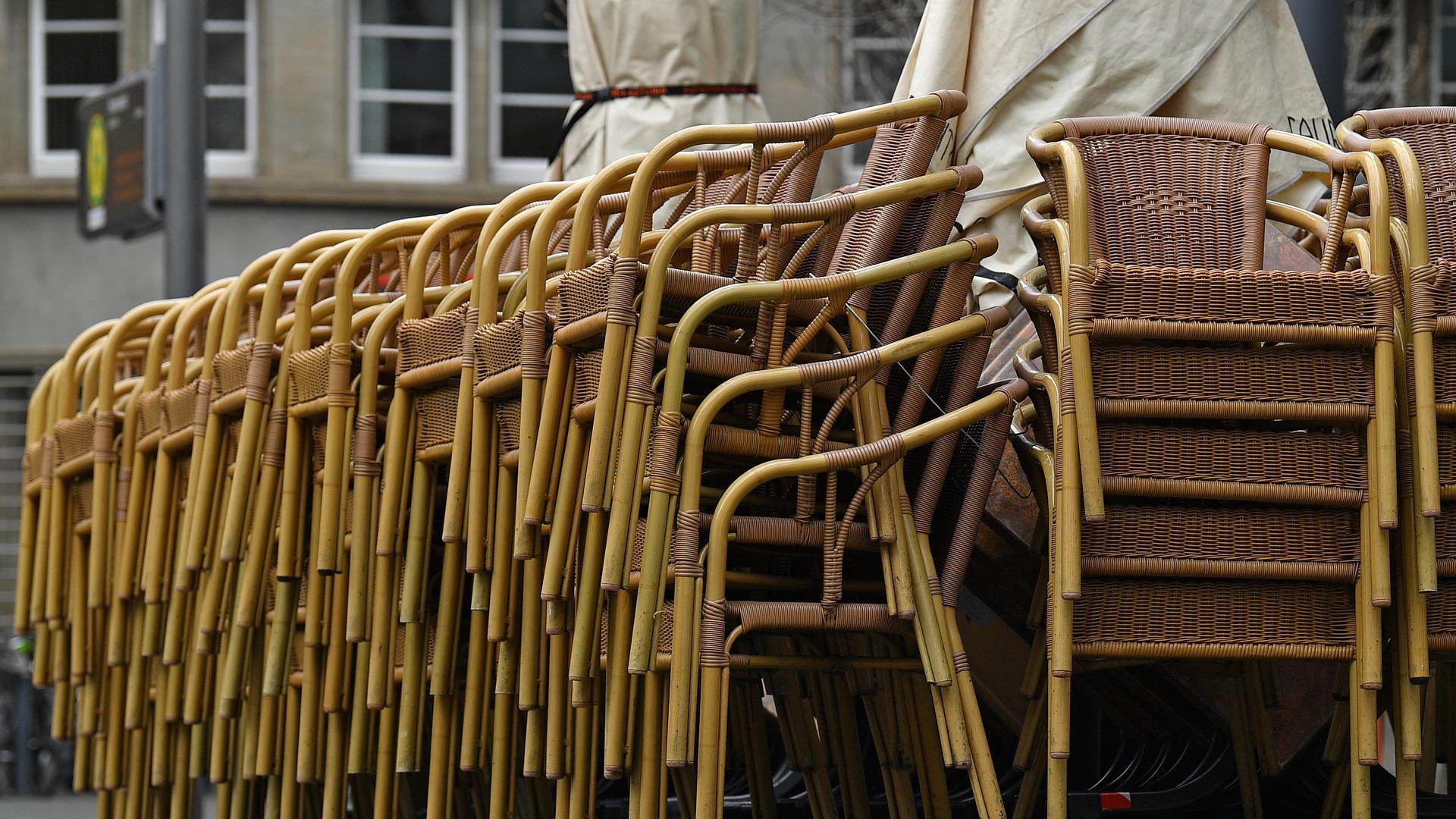Übereinandergestellt sind die Stühle vor einem Restaurant am Fischmarkt. Thüringen ist weiterhin das Bundesland mit der höchsten Sieben-Tage-Inzidenz. +++ dpa-Bildfunk +++