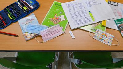 Unterrichtsmaterialien und Masken liegen während einer Pause auf einem Tisch in einem Klassenraum einer Grundschule.