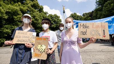 Teilnehmer einer Klimaschutz-Demonstration halten am Friedensengel Schilder mit den Aufschriften «Kohle ist kein Grund zum Anbaggern», «Save the bees» und «Make Love, not CO2!» in den Händen. Die Demonstration unter dem Motto «#TatenStattWorte: Schluss mit den leeren Versprechungen der Söder-Regierung!» wird von Fridays for Future veranstaltet. +++ dpa-Bildfunk +++