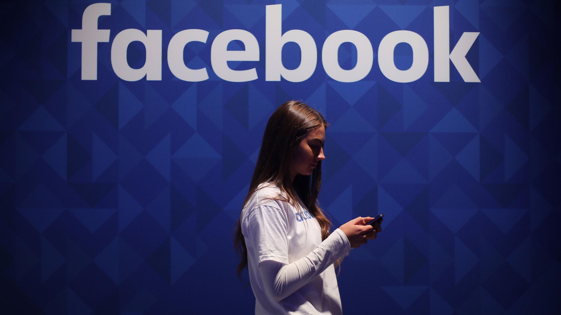 Eine Frau, die ihr Telefon unter einem Facebook-Logo benutzt.