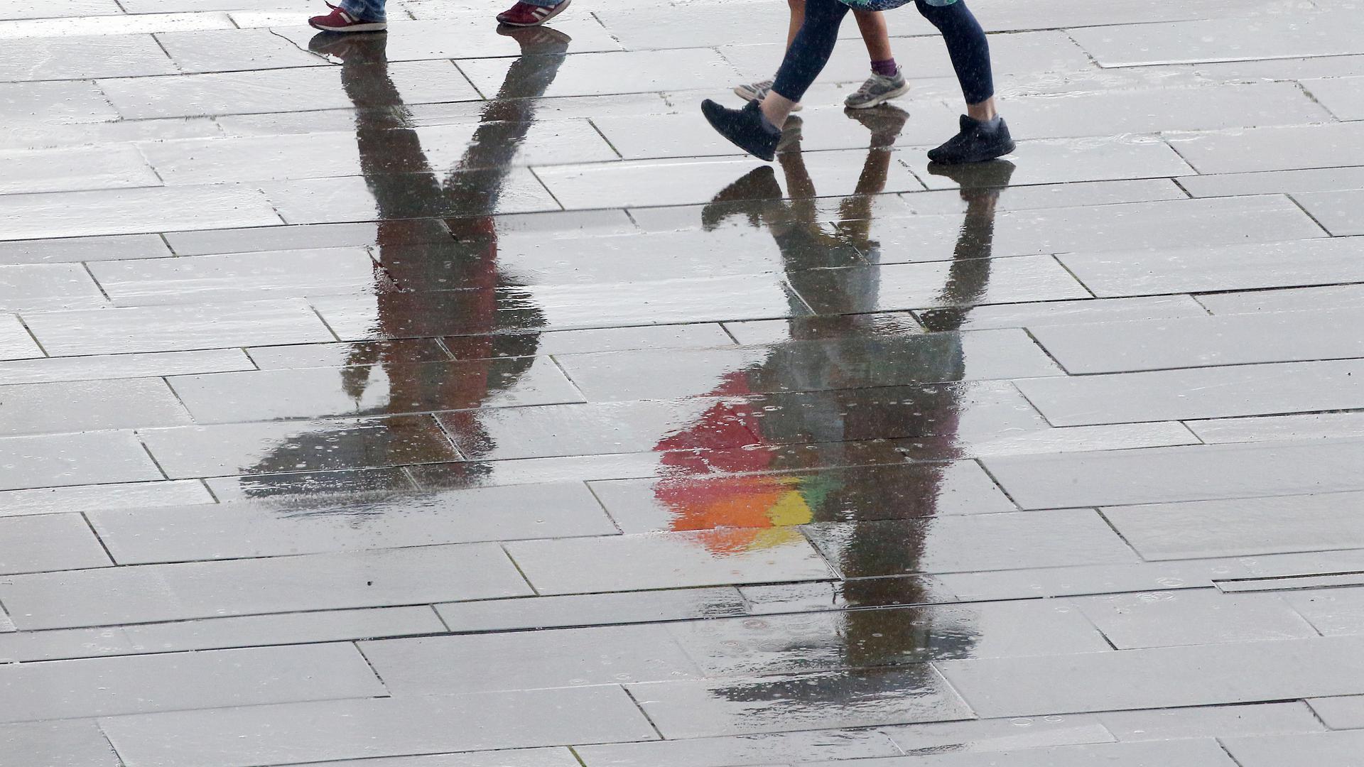 Menschen laufen bei Temperaturen um 15 Grad Celsius mit Regenschirmen durch das Regierungsviertel.