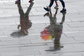 Menschen laufen bei Temperaturen um 15 Grad Celsius mit Regenschirmen durch das Regierungsviertel. Nach Angaben der Meteorologen wird auch in den kommenden Tagen mit schauerartigen Regenfällen zu rechnen sein. +++ dpa-Bildfunk +++