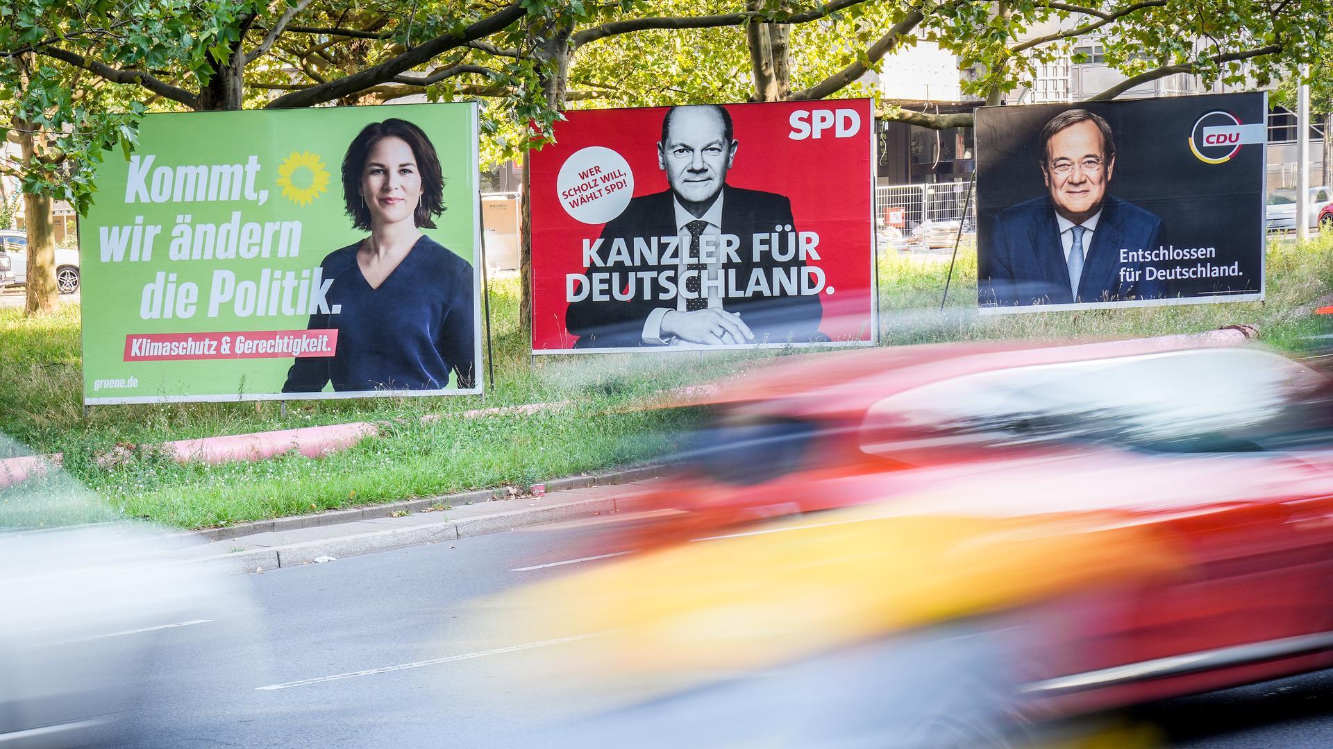 Autos fahren am Morgen an den Wahlplakaten von Bündnis 90/Die Grünen (l-r) mit Kanzlerkandidatin Annalena Baerbock, SPD mit Kanzlerkandidaten Olaf Scholz und CDU mit Kanzlerkandidaten Armin Laschet vorbei. Am 26.09.2021 wird ein neuer Bundestag gewählt. +++ dpa-Bildfunk +++