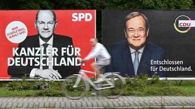 Ein Radfahrer fährt an großen Wahlplakaten mit den Spitzenkandidaten Olaf Scholz (SPD, l) und Armin Laschet (CDU) vorbei.