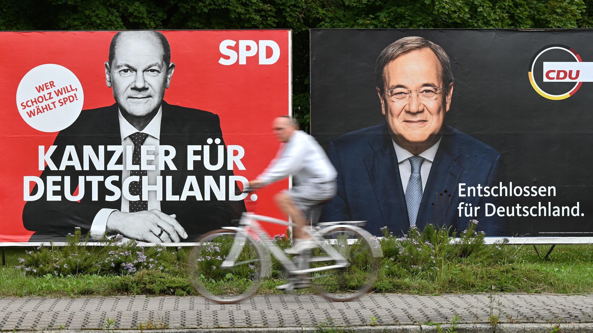 Ein Radfahrer fährt an großen Wahlplakaten mit den Spitzenkandidaten Olaf Scholz (SPD, l) und Armin Laschet (CDU) vorbei (Aufnahme mit längerer Verschlusszeit). Am 26. September 2021 entscheiden die Wählerinnen und Wähler über den neuen Bundestag. +++ dpa-Bildfunk +++