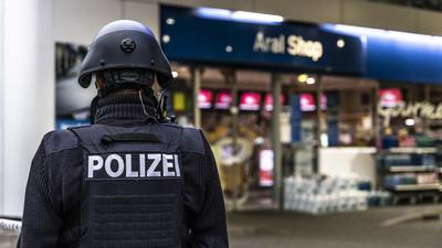 Ein Polizist sichert am frühen Morgen eine Tankstelle. Ein Angestellter der Tankstelle war in Idar-Oberstein in Rheinland-Pfalz von einem mit einer Pistole bewaffneten Mann erschossen worden.