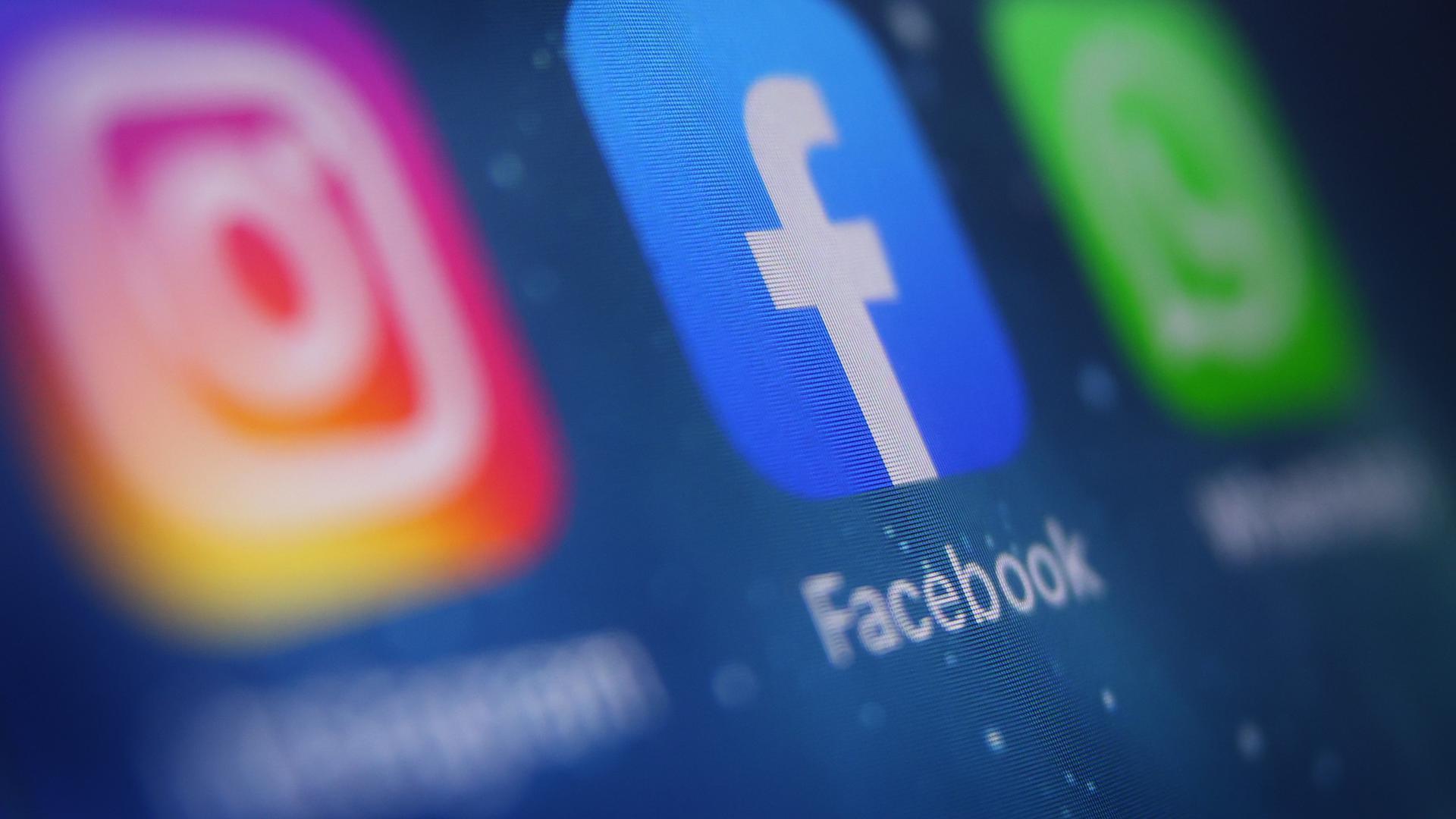 Auf dem Bildschirm eines Smartphones sind die Icons von Instagram, Facebook und WhatsApp zu sehen.