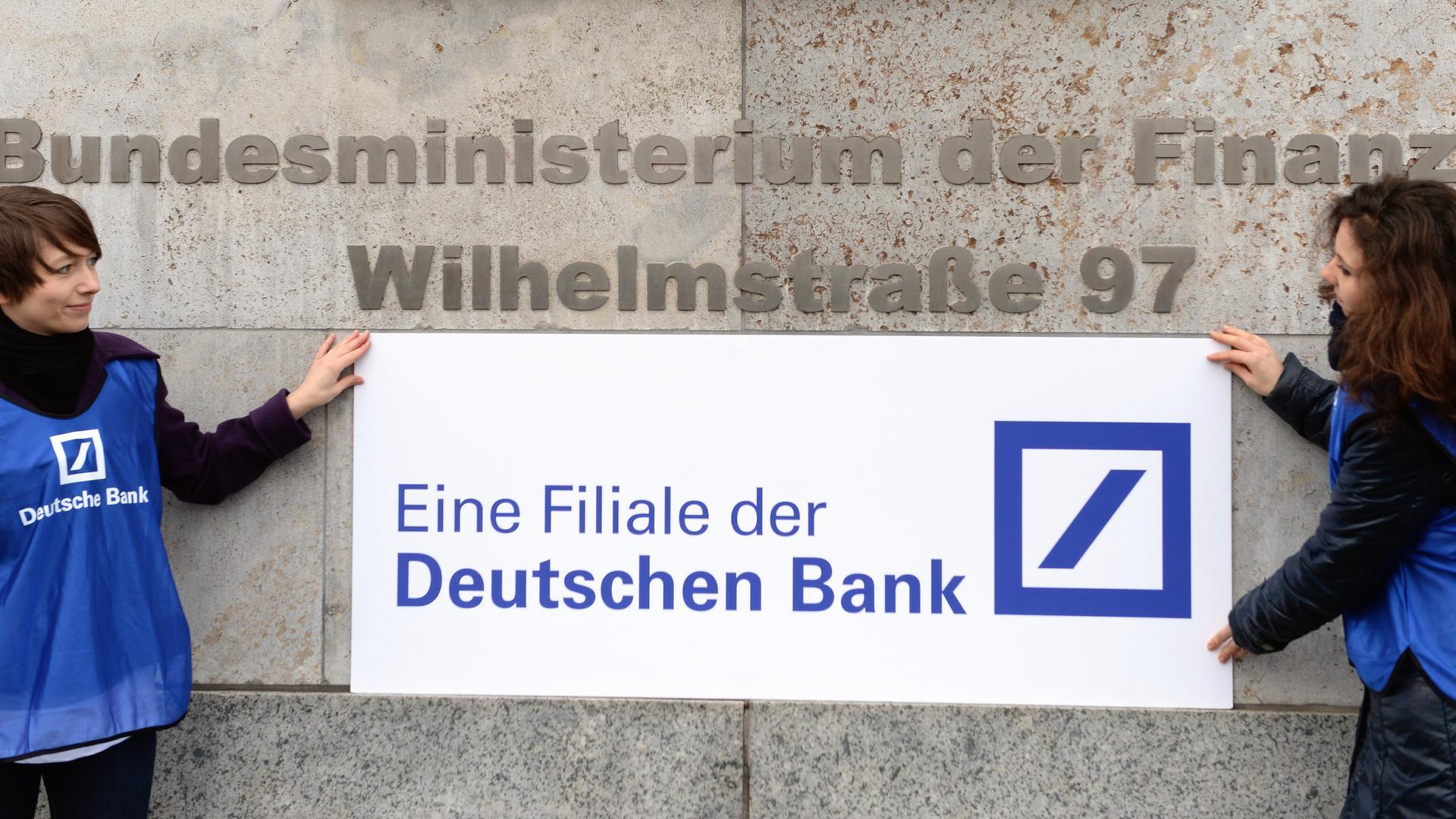 Demonstranten der Verbraucherschutzorganisation foodwatch befestigen am 17.01.2014 am Eingang zum Bundesfinanzministerium in Berlin ein Transparent mit der Aufschrift «Eine Filiale der Deutschen Bank». Die Aktion richtete sich gegen Spekulationsgeschäfte von Banken mit Nahrungsmitteln, die nach Ansicht von foodwatch auch nach den EU-Regeln zur Regulierung der Finanzmärkte nicht gestoppt werden. Foto: Soeren Stache/dpa ++