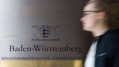 Eine Frau geht in Stuttgart an dem Logo des Ministeriums für Kultus, Jugend und Sport vorbei.