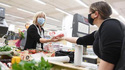 22.04.2020, Bayern, Rosenheim: Eine Kundin wird in einem Lebensmittelgeschäft in der Gemüseabteilung bedient und trägt eine Maske als Mund- und Nasenschutz. In Rosenheim gilt wegen der Corona-Pandemie ab Mittwoch eine Maskenpflicht. Wer ein Geschäft besucht oder den Nahverkehr nutzt, muss in Stadt und Landkreis Mund und Nase verhüllen. Foto: Tobias Hase/dpa +++ dpa-Bildfunk +++ | Verwendung weltweit